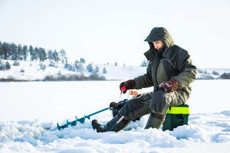 A young man is fishing from a hole on ice. Winter fishing. 版權商用圖片