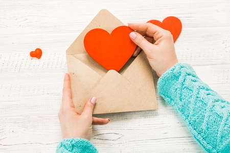 Hand of girl writing love letter on Saint Valentines Day. Handmade postcard with red heart shaped figure. 14 February holiday celebration. Valentine day concept with copy space