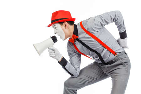 Clown, MIME, holding a Megaphone. The expression of emotions. On a white background. Stock Photo