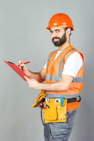 A builder in an orange helmet on a gray background signs something.