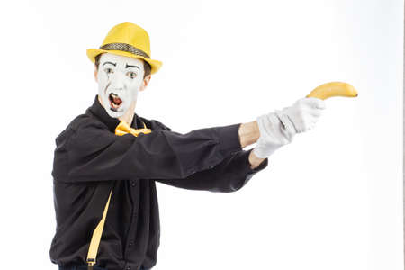 Portrait of a pantomime in the form of a criminal, ganster. Race to the bandit. Holds a banana in his hand in the form of an orgy. Isolated on white background.