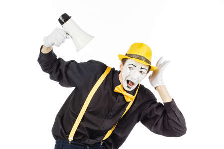 Portrait of a male mime artist, shouting or showing on a megaphone. Isolated on white background. Stock Photo