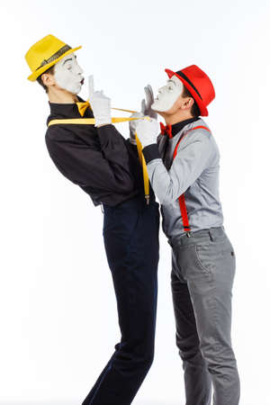 Two young men, an actor, a MIME, in clothing and makeup, argue, and gesticulate on a white background. The expression of emotions.