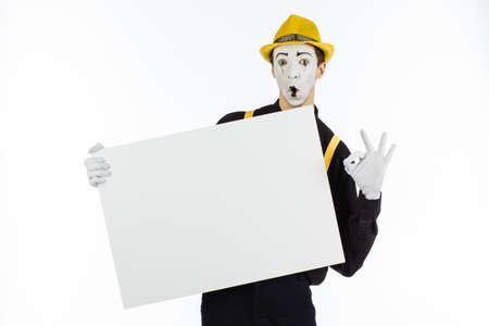 MIME, actor, young man holding white panel with space for text on white background.