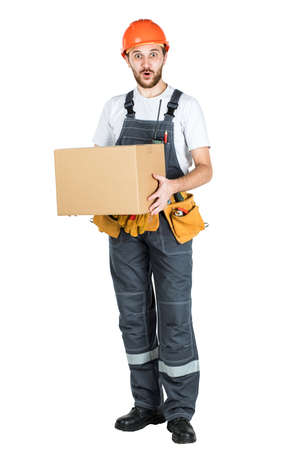 A man is a builder with a cardboard box in his hands. Isolated over white background Stockfoto