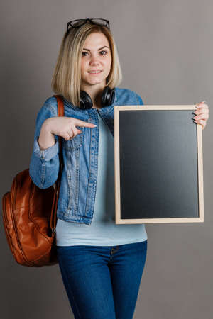 A student woman is holding a blackboard on a gray background. woman and way of life. 스톡 콘텐츠