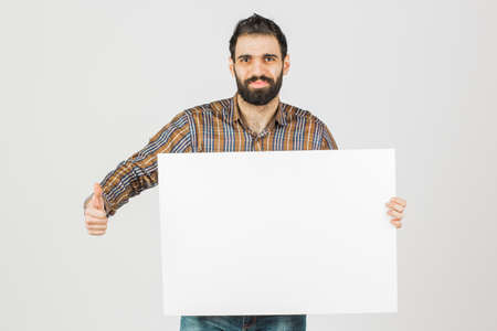 Portrait of a bearded businessman holding a white  blank panel with space for text. Isolated on white background.
