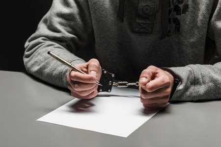 Hands of the criminal in handcuffs write a handle on paper. Sincere confession, request, statement. Justice. Reklamní fotografie