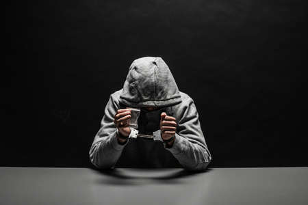 The drug addict was arrested for drug use at the table. suffering from addiction on a dark black background Stock Photo