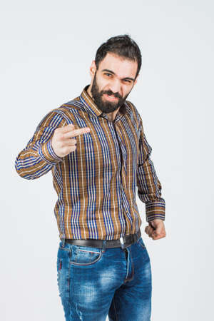 portrait of a serious young bearded man wearing a shirt shows a gesture with the middle finger. isolated on white