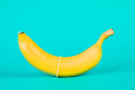Condom and banana on a blue background close-up. Archivio Fotografico
