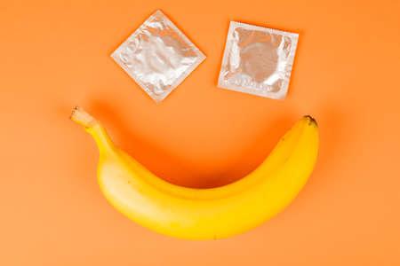 Een condoom en een banaan, veilige seks. Seksspeeltje. Anticonceptie. op een oranje achtergrond Stockfoto
