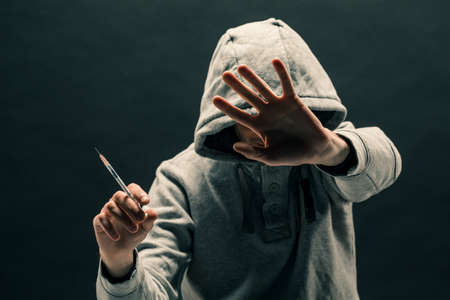 Addict in gray hoodie on the head suffers from addiction on a dark black background.