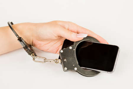 handcuffs connects the female hand and the smartphone together. the concept of dependence on mobile phone.