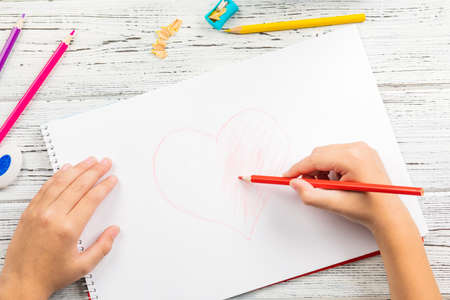 Hand of children drawing red heart with colored pencil on white paper on wooden table