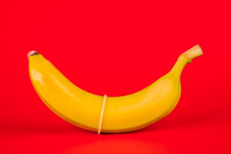 Condom and banana on a red background close-up.