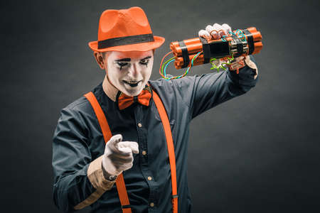 Funny clown with the stick of dynamite on the grey background. Stock Photo