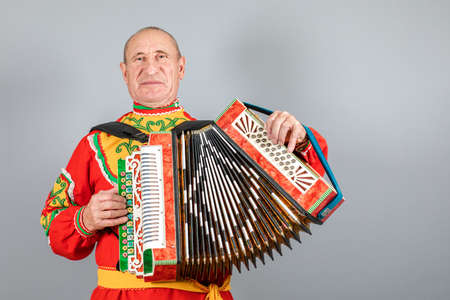 Portrait of a man in a national costume, grandfather plays the accordion. On a gray background