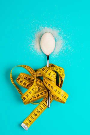 Sugar-replacing tablets or sugar with a spoon are entangled in the measuring tape. On a blue background. The concept of diabetes and proper nutrition. 版權商用圖片