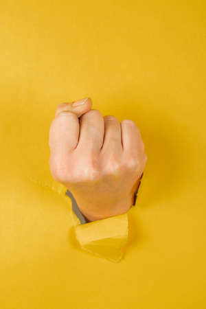 female fist punching through a paper, isolated on a yellow background