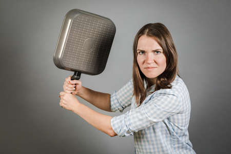 A woman threatens you with a frying pan. On a gray background Banco de Imagens