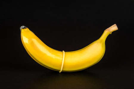 Condom and banana on black background close up. Stock Photo