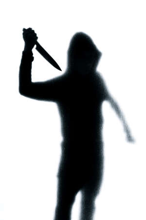 Dangerous man behind frosted glass with a knife in his hand. Halloween. Black and white image Banque d'images