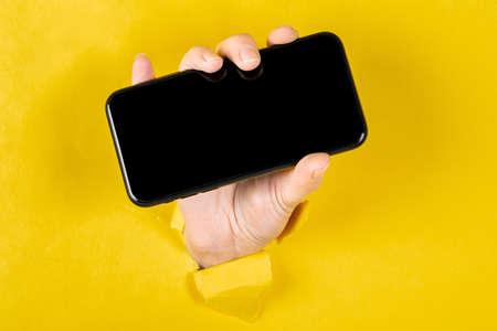 Une femme tenant un téléphone à travers un papier jaune déchiré Banque d'images