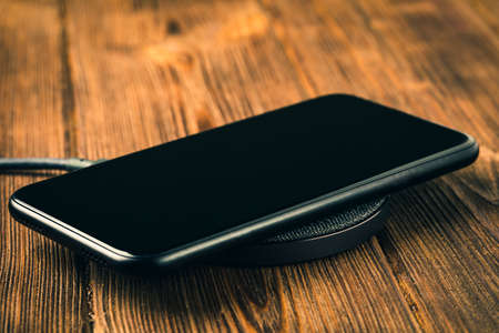 Charge your smartphone on the charging pad. Wireless charging on wooden table. rendered image
