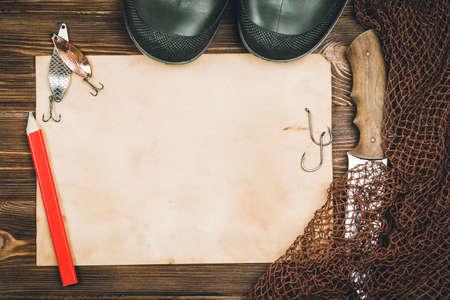 Fishing tackle-fishing, pen, hooks, wooden background.
