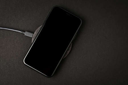 Smartphone is charged by a wireless charger on a black background. The concept of new technologies.