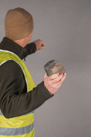 Rebel or protesting worker in a yellow vest with a brick in his hands on a gray background.