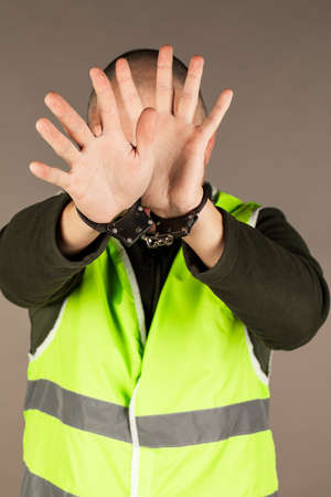man in the yellow vest is handcuffed