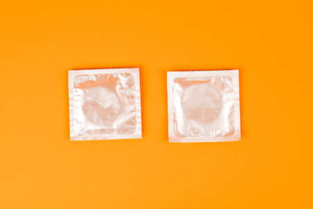 Condoms on an orange background. The concept of prevention and safe sex Stock Photo