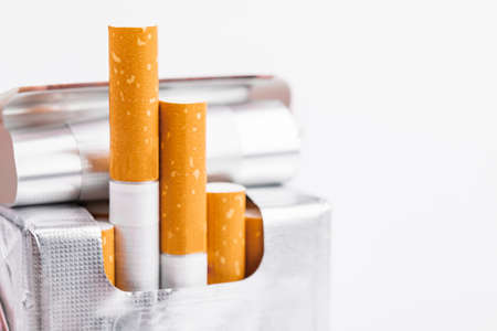 Sigarette in un primo piano del pacchetto su priorità bassa bianca. Tabacco da fumo. Cattiva abitudine. Archivio Fotografico