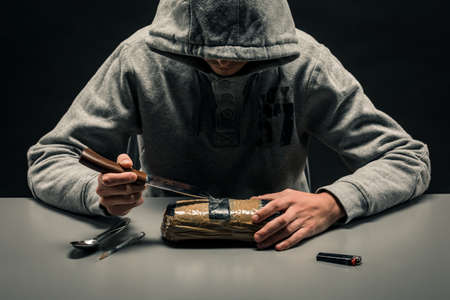 man is a drug addict sitting at the table makes drugs. The concept of social problems of drug addiction and crime.