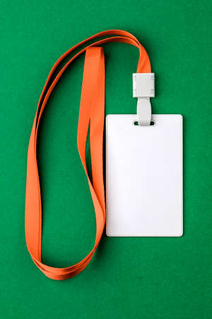 Blank security tag with a red stripe neck on a green background. Place for text, layout.