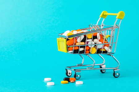 Shopping cart filled with pills. Blue background. Concept: full set of medicines in the store. Copy space for text