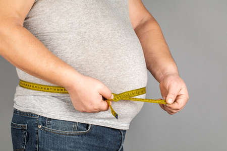 A man measures his fat belly with a measuring tape. on a gray background