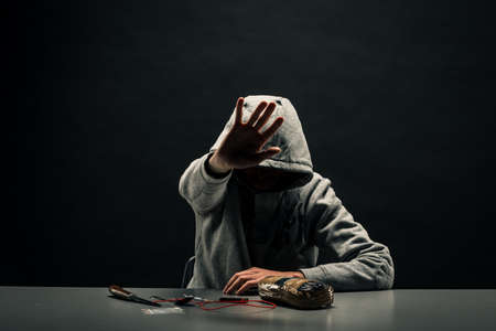 A man sitting at a table with drugs, hides his face Concept: a criminal with drugs