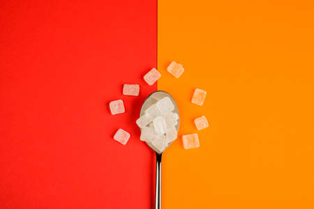 Sugar-replacing tablets spoon on orange and red background.