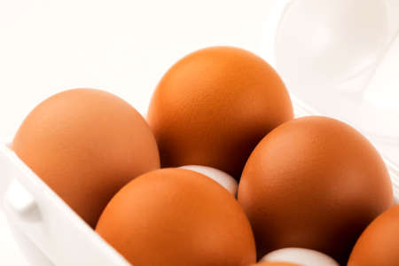 brown eggs in plastic package on white background