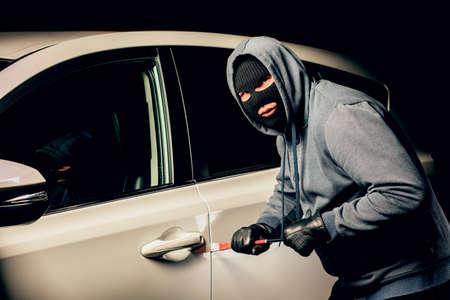 männlicher Dieb wird die Autotür mit einem Brecheisen öffnen