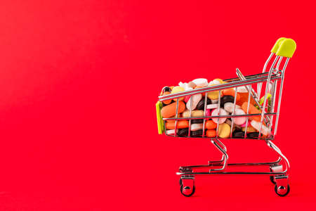 Cart of pills. Red background. Concept: a complete set of medicines in the store. Copy space for text.