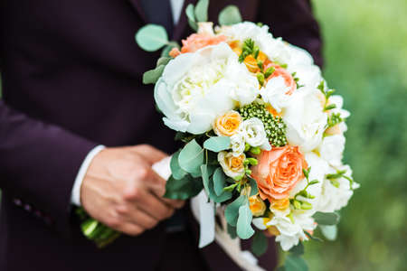 A beautiful bouquet of mixed flowers in the hand of the groom in a suit. Wedding bouquet of fresh flowers for the bride.