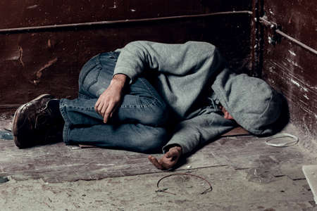 homeless guy sleeps on the floor in the slums.