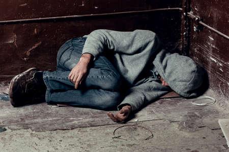 Un vagabundo duerme en el suelo de los barrios marginales.