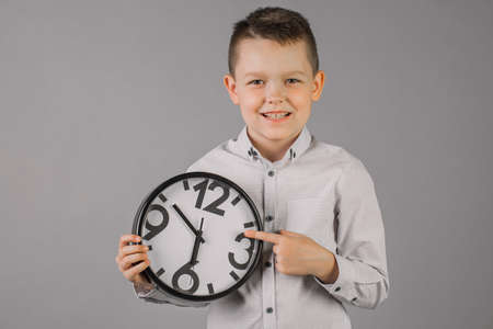 boy wearing a plaid shirt and holding a watch, on a gray wall background, children portrait Studio. People sincere emotions, the concept of children's lifestyle. Copy space layout.