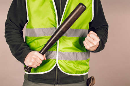 man in a yellow vest, a Builder or a protester with a baseball bat in his hands on a gray background. Foto de archivo