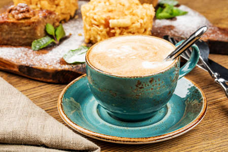 Cappuccino Cup with latte on wooden background. Beautiful foam, green ceramic Cup Foto de archivo